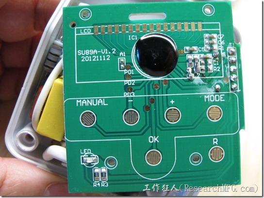 數位式定時器拆解。LCD顯示器其實可以很輕鬆的就拿開,顯示器的下面可以看到LCD的導電接觸墊,這是給導電斑馬條用來導通LCD用的。另外,還可以看到一顆用黑色環氧樹脂膠(Epoxy)封住的COB晶片,這一顆應該就是整個數位定時器的靈魂控制晶片了,它應該可以控制LCD的顯示以及處理所有按鍵的動作,包括控制繼電器的點源開啟或關閉。