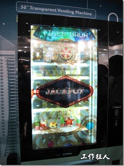 """這是友達的穿透液晶螢幕(50"""") ,它被應用到自動販賣機,作成類似吃角子老虎的設計,讓客戶可以清楚螢幕後方的販賣機賣些什麼物品。"""