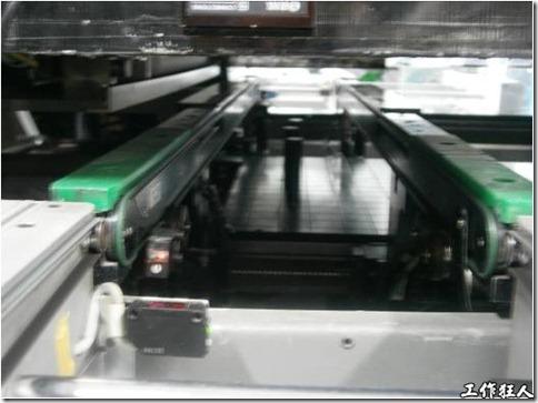 DEK錫膏印刷機的側面顯示傳送電路板的皮帶,萬用支撐柱放置與兩條皮帶的中間。