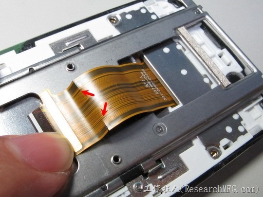 拆開這支W100i後,發現這款手機連接上、下機殼間的軟排線(FPC)已經斷裂了,而且斷裂處剛好就在金屬鐵片(sheet metal)的斷面上